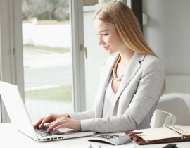 Attractive businesswoman sitting at desk and typing on keyboard in office.