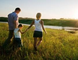 młoda, szczęśliwa rodzina z dzieckiem spaceruje po łące