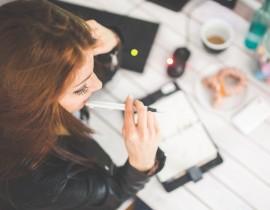 Kobieta robiąca notatki pracująca przy komputerze