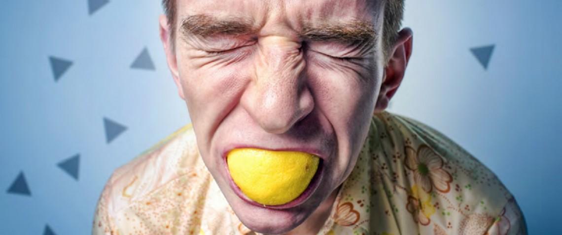 Mężczyzna gryzący cytrynę